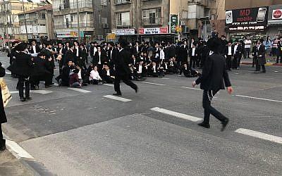 Des manifestants ultra-orthodoxes bloquent une route à Bnei Brak alors qu'ils manifestent contre le projet de l'armée, le 22 mars 2018 (Crédit : Porte-parole de la police)