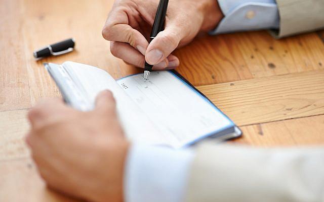 Illustration: Un homme écrit un chèque (Crédit :  PeopleImages/Getty Images via JTA)