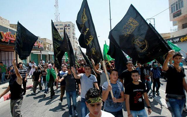 Les partisans palestiniens du Jihad islamique brandissent des drapeaux lors d'un rassemblement pour soutenir les habitants de la bande de Gaza le 15 août 2014 à Bethléem en Cisjordanie (Crédit : AFP / Musa al-Shaer)