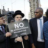 David Lammy (2 à droite), membre du Parti travailliste britannique, se joint aux membres de la communauté juive qui manifestent contre le chef du parti travailliste britannique Jeremy Corbyn et l'antisémitisme au sein du parti travailliste devant les chambres du Parlement britannique dans le centre de Londres le 26 mars 2018 (Crédit : AFP PHOTO / Tolga AKMEN)