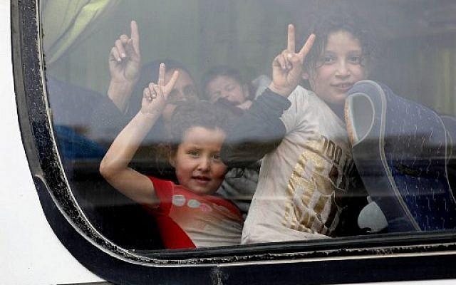 Des enfants syriens évacués de la région de la Ghouta orientale à la fenêtre d'un bus alors qu'ils arrivent à Qalaat al-Madiq, à 45 kilomètres au nord-ouest de la ville de Hama, le 28 mars 2018, suite à un accord d'évacuation entre la faction rebelle islamiste Faylaq al-Rahman, qui contrôle une partie de la Ghouta, et la Russie, un allié du président syrien (AFP PHOTO / OMAR HAJ KADOUR)