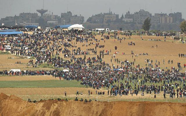 Une photo prise le 30 mars 2018 du kibboutz israélien sud de Nahal Oz de l'autre côté de la bande de Gaza montre des Palestiniens participant à une manifestation pour commémorer la Journée de la Terre(Crédit : AFP PHOTO / Jack GUEZ)