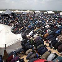 Les fidèles musulmans font la prière du vendredi, à midi, près d'une ville en tentes aux abords de la frontière avec Israël, à l'est de Jabalia, le 30 mars 2018 (Crédit : AFP/Mohammed Abed)