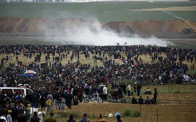 Les Palestiniens participent à des manifestations aux abords de la frontière avec Israël, à l'est de Jabalia, dans le nord de la bande de Gaza, le 30 mars 2018 (Crédit : AFP/Mohammed Abed)