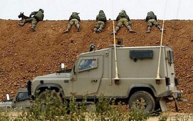 Des soldats israéliens sur la barrière terrestre le long de la frontière avec Gaza, à proximité du kibboutz israélien de  Nahal Oz, dans le sud du pays, le 30 mars 2018 (Crédit : Jack Guez/AFP)