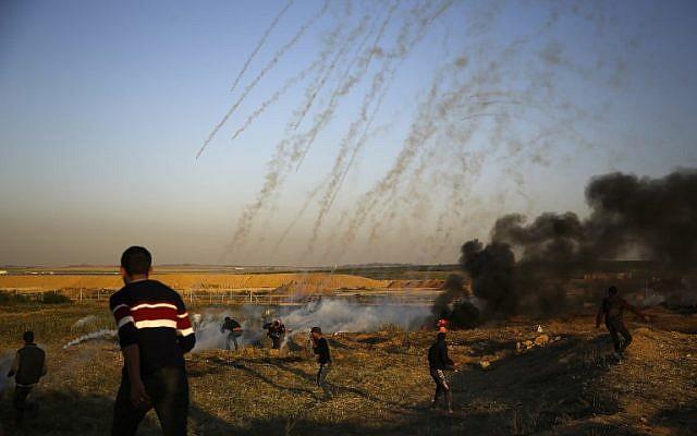 Des manifestants palestiniens courent pour échapper au gaz lacrymogène lancé par les forces israéliennes durant des affrontements qui ont suivi une manifestation le long de la frontière avec Israël, à l'est de  Gaza City, le 1er avril 2018 (Crédit : Mohammed Abed/AFP)