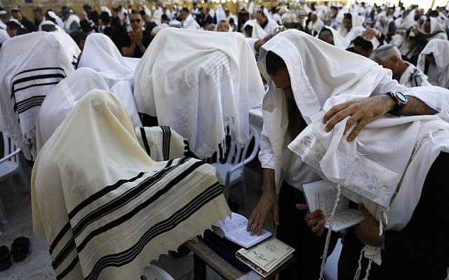 """Des Cohanim recouverts de leur """"Talit"""" (châles de prière) lors de la bénédiction des Cohanim pendant la fête de Pessah (Pessah) au mur Occidental dans la Vieille Ville de Jérusalem, le 2 avril 2018. (AFP PHOTO / MENAHEM KAHANA)"""