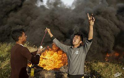 Des manifestants palestiniens scandent des slogans durant des affrontements avec les forces israéliennes suite à un rassemblement à la frontière entre Israël et Gaza, à l'est de Gaza City, le 4 avril 2018 (Crédit :  AFP PHOTO / MAHMUD HAMS)