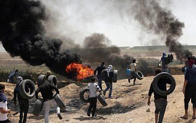 Des hommes palestiniens collectent des pneus et les brûlent pour se protéger des tirs de soldats israéliens à la frontière entre Israël et Gaza lors d'une manifestation à l'est de la ville de Gaza, le 6 avril 2018 (Crédit : AFP PHOTO / MAHMUD HAMS)
