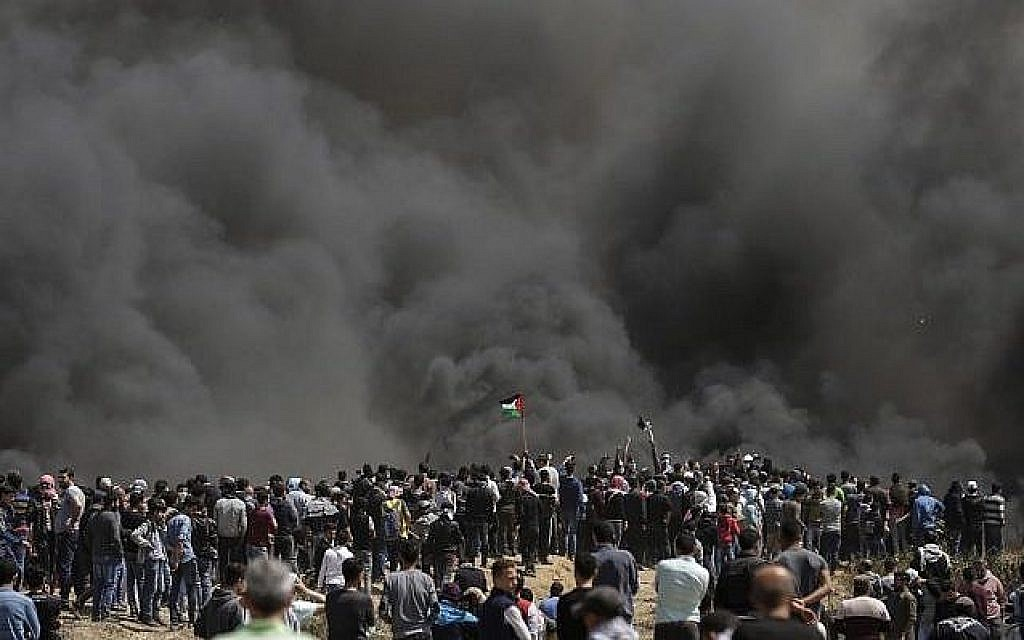 Des Palestiniens brandissent leurs drapeaux sous une forte fumée de pneus brûlés par les Gazaouis à la frontière entre Israël et Gaza lors d'une manifestation, à l'est de la ville de Gaza, le 6 avril 2018 (AFP PHOTO / MAHMUD HAMS)