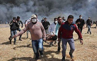Photo d'illustration : un manifestant palestinien blessé est porté par des manifestants lors d'affrontements avec les forces de sécurité israéliennes près de la frontière avec Israël, à l'est de Khan Younis, dans le sud de la bande de Gaza, le 6 avril 2018 (AFP / Said Khatib)
