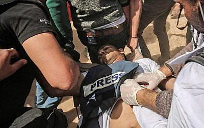 Des manifestants aident le journaliste palestinien blessé Yasser Murtaja lors d'affrontements avec les forces de sécurité israéliennes, à la suite d'une manifestation près de la frontière avec Israël, à l'est de Khan Younès, dans le sud de la bande de Gaza, le 6 avril 2018. Il a succombé à ses blessures. (AFP PHOTO / DIT KHATIB)