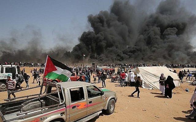 Des manifestants palestiniens brûlent des pneus pendant des affrontements avec les forces de sécurité israéliennes sur la frontière entre Gaza et Israël, le 6 avril 2018 (Crédit : AFP PHOTO / SAID KHATIB)