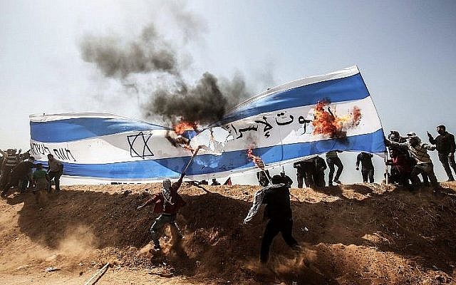 Des émeutiers palestiniens brûlent un drapeau israélien lors d'affrontements avec les forces de sécurité israéliennes à la frontière entre Gaza et Israël, à l'est de Khan Younis, dans le sud de la bande de Gaza, le 6 avril 2018. (Crédit : AFP / SAID KHATIB)