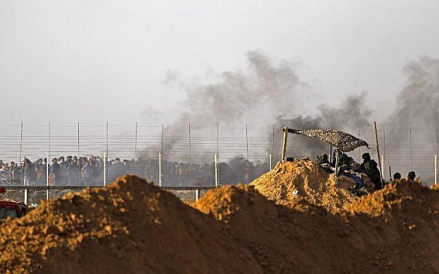 Les forces israéliennes déployées aux abords du  Kibbutz Kerem Shalom sur la frontière israélienne au sud de la bande de Gaza alors que la fumée de pneus brûlés par les Palestiniens se dégage, le 6 avril 2018 (Crédit : AFP PHOTO / MENAHEM KAHANA