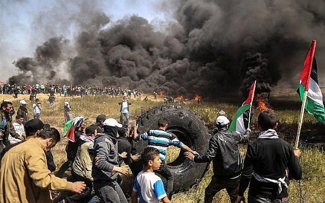Des manifestants palestiniens brûlent des pneus lors d'affrontements avec les forces de sécurité israéliennes à la frontière entre Gaza et Israël, à l'est de la ville de Gaza, le 6 avril 2018. (AFP PHOTO / MAHMUD HAMS)