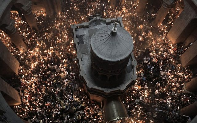 """Les fidèles chrétiens orthodoxes tiennent des bougies allumées au """"feu sacré"""" lors d'un rassemblement à l'église du Saint-Sépulcre de la Vieille Ville de Jérusalem lors de la Pâque orthodoxe, le 7 avril 2018. (Crédit : AFP PHOTO / GALI TIBBON)"""