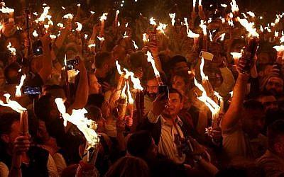"""Les fidèles chrétiens orthodoxes tiennent des bougies allumées au """"feu sacré"""" lors d'un rassemblement à l'église du Saint-Sépulcre de la Vieille Ville de Jérusalem lors de la Pâque orthodoxe, le 7 avril 2018   (Crédit : AFP PHOTO / GALI TIBBON)"""