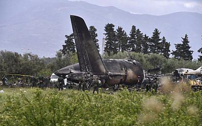 Des secouristes autour des débris d'un avion algérien qui s'est écrasé près de la base aérienne de Boufarik d'où l'avion avait décollé le 11 avril 2018. L'avion militaire s'est écrasé et a pris feu, tuant 257 personnes, principalement des militaires et des membres de leurs familles (Crédit : Ryad Kramdi / Photo AFP)
