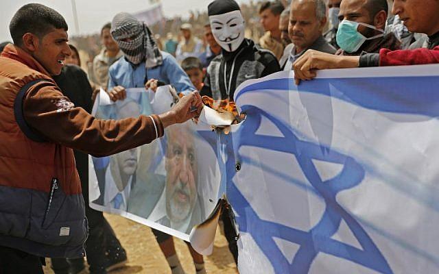 Les Palestiniens s'apprêtent à mettre le feu sur un drapeau israélien et des portraits du ministre de la Défense Avigdor Liberman et du Premier ministre Benjamin Netanyahu lors d'une manifestation à la frontière avec Israël, à l'est de Khan Yunis dans le sud de Gaza le 13 avril 2018 (Crédit : AFP PHOTO / Thomas COEX)