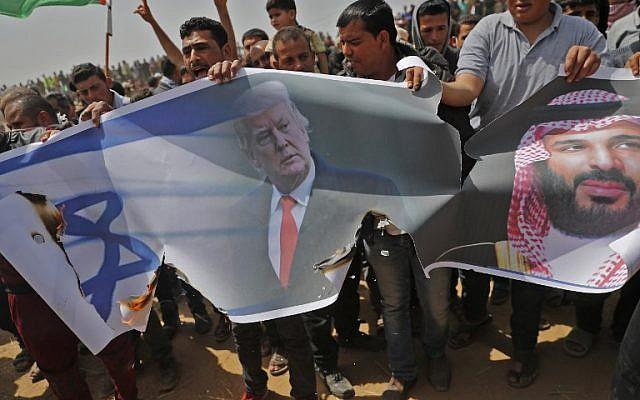Les Palestiniens s'apprêtent à incendier un drapeau israélien et des portraits du président américain Donald Trump et du prince héritier saoudien Mohammed ben Salmane lors d'une manifestation contre la barrière frontalière avec Israël, à l'est de Khan Yunis, au sud de Gaza le 13 avril 2018 (Crédit :  AFP PHOTO / Thomas COEX)