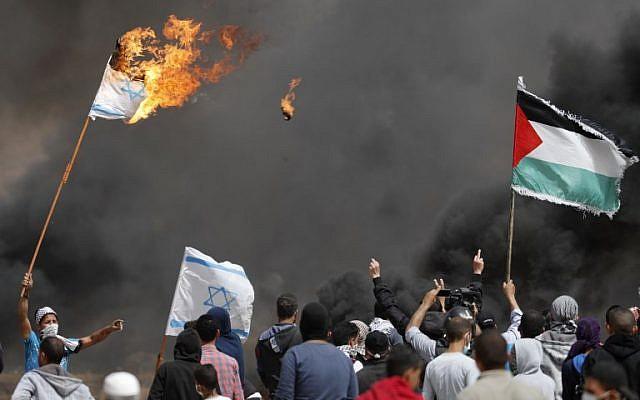 Des manifestants palestiniens brûlent des drapeaux israéliens près de la barrière frontalière avec Israël, à l'est de Khan Yunis dans le sud de la ville de Gaza, le 13 avril 2018 (Crédit : AFP / Thomas Coex)