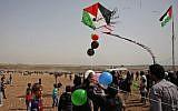 Des Palestiniens font voler un cerf-volant alors qu'ils se rassemblent à la frontière avec Israël, à l'est de Jabalia, dans le centre de la ville de Gaza, lors d'une manifestation le 13 avril 2018 (Crédit : AFP / Mohammed Abed)