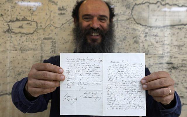 Meron Eren, co-fondateur et propriétaire de la maison d'enchères Kedem, tient une lettre du compositeur antisémite allemand Richard Wagner à Jérusalem le 16 avril 2018. (Crédit : Menahem Kahana / AFP)