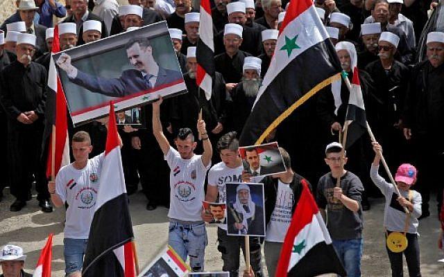Les habitants druzes du village d'Ein Qiniye dans les hauteurs du Golan brandissent des drapeaux syriens et des images du président syrien lors d'un rassemblement marquant le Jour de l'Indépendance de la Syrie le 17 avril 2018. (Crédit : AFP / JALAA MAREY)