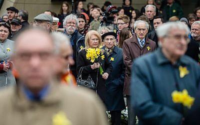 Sur cette photo prise le 19 avril 2016, les gens se rassemblent devant le monument du Soulèvement du ghetto de Varsovie, où l'on voit des jonquilles à l'occasion du 73e anniversaire du soulèvement du ghetto de Varsovie (Crédit : AFP PHOTO / WOJTEK RADWANSKI)