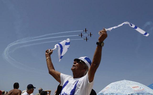 Les Israéliens regardent un spectacle aérien pendant les festivités du 70ème Jour de l'Indépendance, le 19 avril 2018 dans la ville côtière méditerranéenne de Tel Aviv (Crédit : AFP PHOTO / Ahmad GHARABLI)