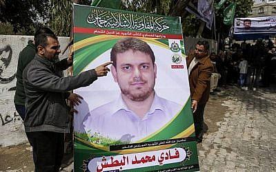 Une photo prise le 21 avril 2018 montre des hommes tenant une affiche du professeur palestinien de 35 ans et membre du Hamas Fadi Mohammad al-Batsh qui a été tué en Malaisie, devant la maison de sa famille à Jabaliya dans le nord de la bande de Gaza. (AFP PHOTO / MAHMUD HAMS)