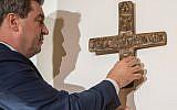 Cette photo prise le 24 avril 2018 à Munich montre Markus Soeder, Premier ministre bavarois, alors qu'il accroche une croix dans l'entrée de la Chancellerie de l'État de la Bavière (Crédit : AFP PHOTO / dpa / Peter Kneffel / Allemagne OUT)