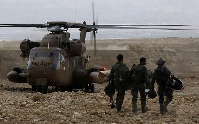 Les soldats se dirigent vers un hélicoptère militaire durant une mission de recherche de plusieurs adolescents portés disparus dans le sud d'Israël après que des inondations subites ont balayé la zone où ils faisaient une randonnée près de la mer Morte le 26 avril 2018 (Crédit : AFP PHOTO / MENAHEM KAHANA)