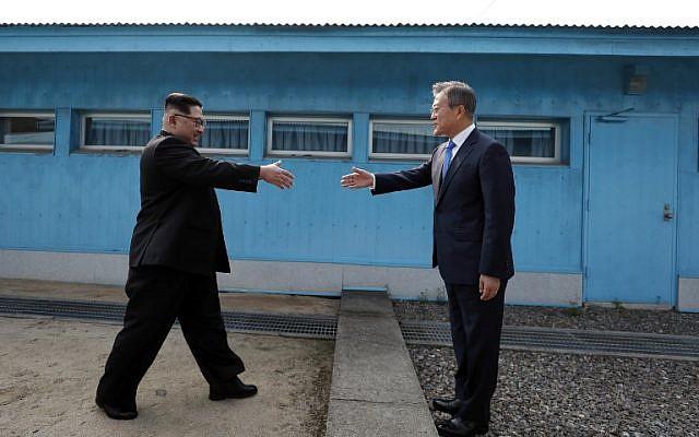 Poignée de main symbolique entre le dirigeant nord-coréen Kim Jong Un et le président sud-coréen Moon Jae-in, à la Ligne de Démarcation militaire qui divise leur pays avant leur sommet à Panmunjom, le 27 avril 2018. (Crédit : AFP / Korea Summit Press Pool / Korea Summit Press Pool)