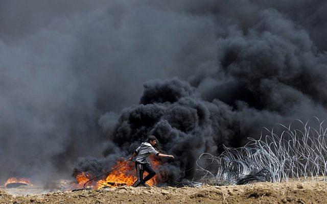 Un Palestinien tente de faire tomber une partie de la barrière frontalière entre Israël et Gaza à l'est de la ville de Gaza, dans le centre de la bande de Gaza, lors du cinquième vendredi consécutif d'émeutes de masse le long de la frontière entre Gaza et Israël, le 27 avril 2018. (AFP Photo/Mahmud Hams)