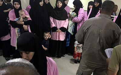 Une photo prise le 29 avril 2018 au tribunal pénal central de Bagdad, la capitale irakienne, montre des femmes russes condamnées à la prison pour avoir rejoint le groupe de l'État islamique debout avec des enfants dans un couloir. (Crédit : AFP/ Ammar Karim)