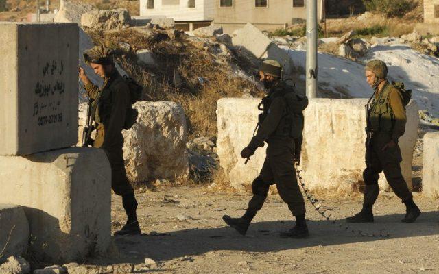 Des soldats de Tsahal transportent des herses à pointes alors qu'ils bloquent une route à l'entrée sud d'Hébron, le 2 juillet 2016, après que les troupes israéliennes ont verrouillé la ville de Cisjordanie à la suite d'une série d'attentats terroristes palestiniens meurtriers. (AFP/Hazem Bader)