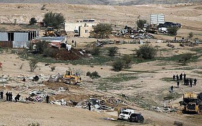Des policiers israéliens montent la garde alors que des bulldozers démolissent des maisons dans le village bédouin illégal d'Oum al-Hiran, dans le désert du Néguev, le 18 janvier 2017. (AFP Photo/Menahem Kahana)