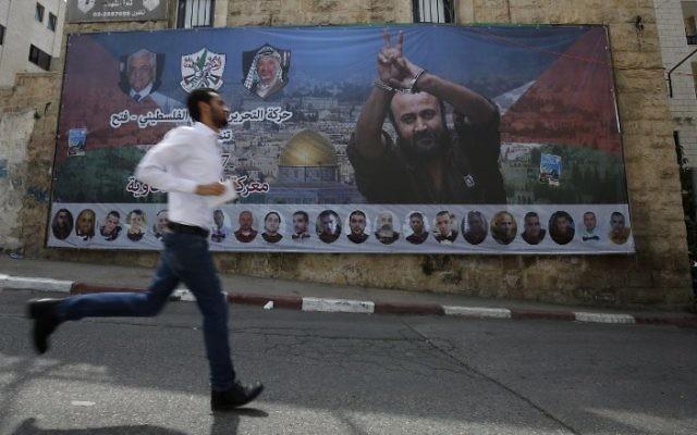 Un Palestinien passe devant une affiche avec le portrait du terroriste condamné et célèbre prisonnier palestinien Marwan Barghouti dans la ville de Ramallah, en Cisjordanie, le 3 mai 2017. (AFP/ ABBAS MOMANI)