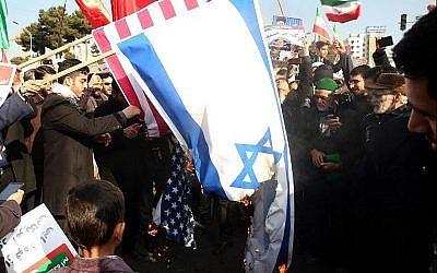 Des partisans iraniens favorables au gouvernement brûlent les drapeaux israéliens et américains lors d'un rassemblement à Mashhad en soutien au régime après que les autorités ont déclaré la fin des récentes manifestations, le 4 janvier 2018 (Crédit : AFP Photo / Tasnim News / Nima Najafzadeh)