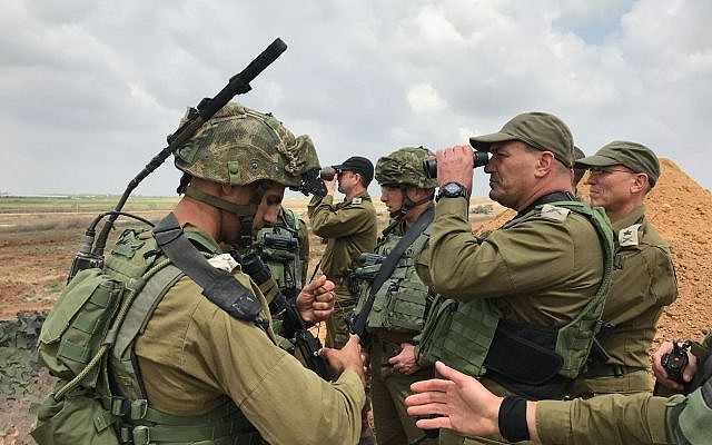 Le chef du Commandement du sud de l'armée israélienne, le général de division  Eyal Zamir,  regarde à travers une paire de lunette pour mieux voir la situation dans la bande de Gaza alors que le chef des opérations de l'armée, le général de division Nitzan Alon, se tient derrière durant une manifestation massive le long de la frontière, le 30 mars 2018 (Crédit : Armée israélienne)