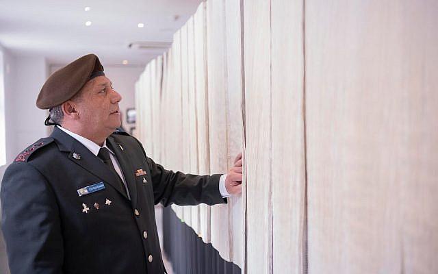 Le chef d'état-major, Gadi Eizenkot, consulte une liste imprimée de toutes les victimes identifiées de l'Holocauste au camp de concentration d'Auschwitz en Pologne le 12 avril 2018. (Crédit : armée israélienne)