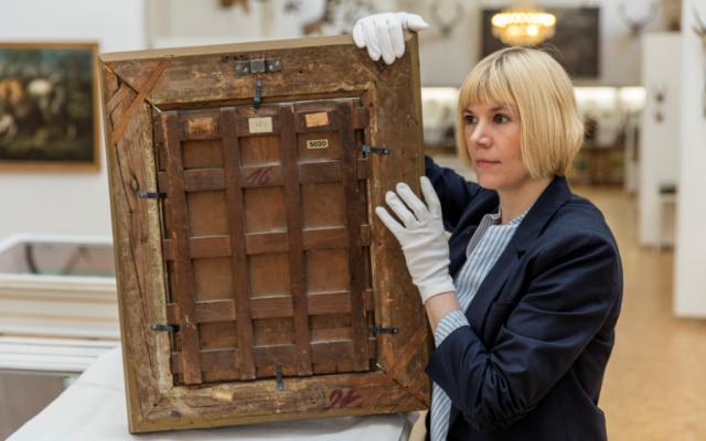 Carolin Lange inspectant le cadre d'une peinture à l'huile. (Office d'État pour les musées non étatiques en Bavière)