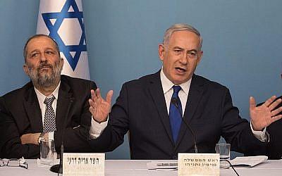 Le Premier ministre Benjamin Netanyahu (à droite) et le ministre de l'Intérieur Aryeh Deri annoncent un nouvel accord sur les réfugiés avec l'ONU, quelques heures avant de le suspendre, le 2 avril 2018 (Hadas Parush/Flash90).