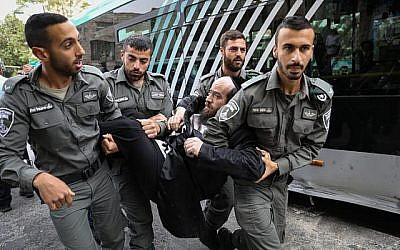 Des hommes juifs ultra-orthodoxes se heurtent à la police lors d'une manifestation contre l'autopsie d'un bébé qui s'est noyé la veille à Ashdod, à Kikar HaShabbat, à Jérusalem, le 3 avril 2018. (Noam Revkin Fenton/Flash90)