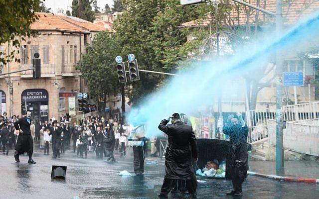 Des hommes juifs ultra-orthodoxes se heurtent à la police lors d'une manifestation contre l'autopsie d'un bébé qui s'est noyé la veille à Ashdod, à Kikar HaShabat, à Jérusalem, le 3 avril 2018. (Noam Revkin Fenton/Flash90)