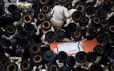 Des hommes juifs ultra-orthodoxes assistent aux funérailles du nourrisson qui s'est noyé dans un hôtel à Ashdod, comme on le voit ici lors de la cérémonie d'inhumation à Jérusalem, le 5 avril 2018. (Noam Revkin Fenton/Flash90)