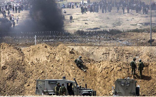 Des manifestants palestiniens brûlent des pneus près de la frontière avec Israël dans la bande de Gaza, vu du côté israélien de la frontière, le 13 avril 2018. (Sliman Khader/Flash90)