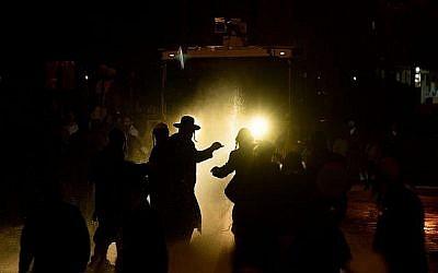 La police israélienne utilise un canon à eau contre les manifestants juifs ultra-orthodoxes lors d'une manifestation devant le bureau de recrutement de l'armée à Jérusalem, à la suite de l'arrestation d'une femme juive ultra-orthodoxe. 15 avril 2018. (Yonatan Sindel/Flash90)